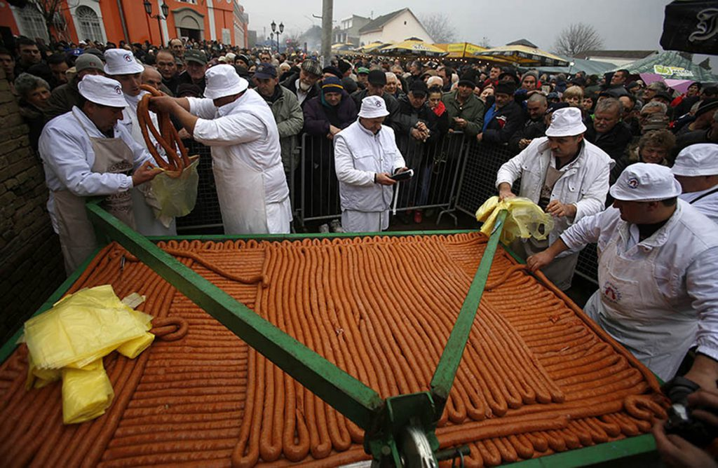 Cooks sell a 2,031 meter-long sausage made for the 31st annual Sausage Festival in the village of Turija, some 100 kilometers (60 miles) northwest of Belgrade, Serbia, Saturday, Feb. 28, 2015. The sausage was made of 3430 kilograms meat from 28 pigs, 60 kilograms of salt, 26 kilograms of ground dried paprika, 5 kilograms of pepper and 5 kilograms of garlic. (AP Photo/Darko Vojinovic)